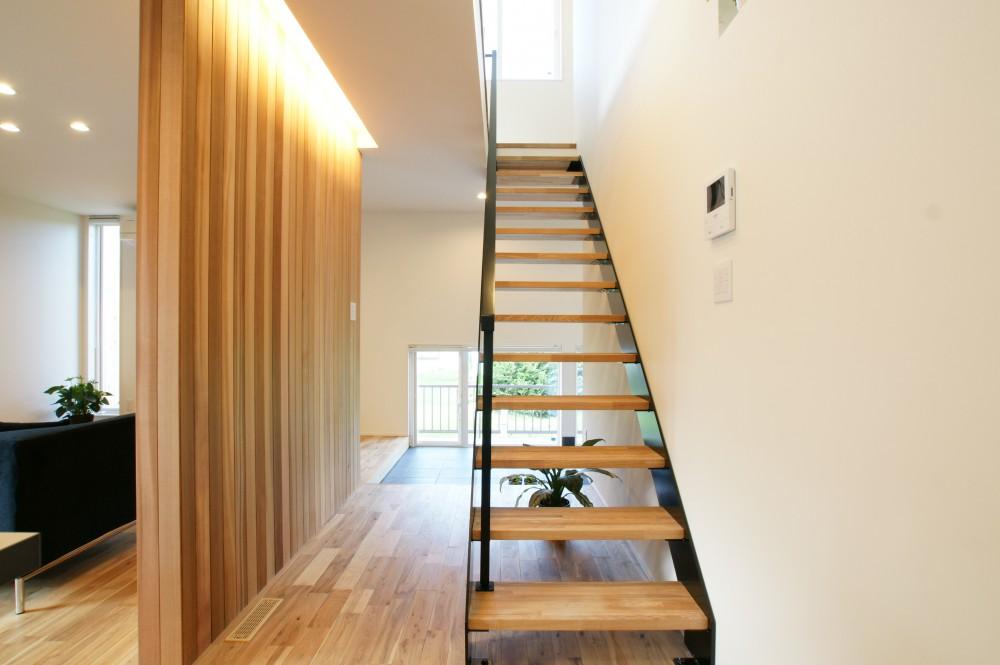 白の外壁に木の板がおしゃれな家